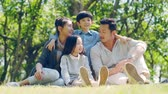 asian family with two children sitting on grass outdoors in a park talking chatting Стоковые видеозаписи