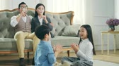 bratr : two asian children sitting on carpet on the floor playing game with mother and father watching from behind Dostupné videozáznamy