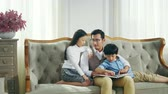 loving asian father and two children reading book together in living room at home