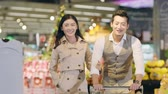 happy young asian couple doing grocery shopping in supermarket Стоковые видеозаписи