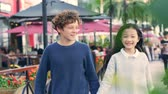 singapore : little caucasian boy and asian girl walking hand in hand on street