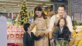 happy asian family with two children doing grocery shopping in supermarket