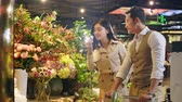 happy young asian couple buying flowers while doing grocery shopping
