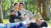 asian parents watching two children lying on grass reading a book together in park