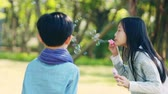 asian little boy and girl playing blowing bubbles outdoors in park