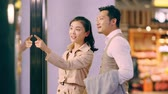 happy asian couple shoppers walking in shopping mall looking into shop window