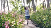 flagstone : 8 year-old beautiful little asian girl running on flagstone path through flower blossoms in park