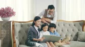 cuentacuentos : asian family with two children reading book together in living room at home