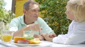 week end : An elderly couple talking in the garden for lunch.