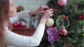 celebration : Pretty girl decorate Christmas tree with balls