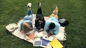 repousante : High angle view of three students reading books Vídeos