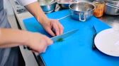 nature close up : The cook cutting the asparagus on the board into a small pieces.
