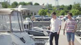 аренда : Salesman and buyer walk along the pier and examine yachts. Man wearing stripped T-shirt ask the seller about kinds of yachts and their details. Young man come to yacht club to buy a yacht.