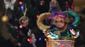 bead : Beautiful joke toy. Doll in beautiful bright clothes moves from side to side. Christmas tree with Christmas balls on the background. Close-up. Stock Footage