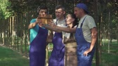 produtividade : Gardeners make selfie in the garden. Three men and woman have fun at work. People do their work carefully Vídeos