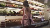 caixa : Beautiful little girl puts the vegetables and fruits in a basket at the supermarket. Pretty little girl buys groceries in the store. Cute girl at the grocery store. Vídeos