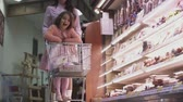 potomstvo : Mom carries little daughter on a cart with products in the store. Young woman with her daughter in the store together. Shopping at the grocery store.