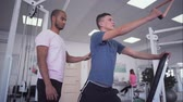 разработка : African-american coach helps young guy to train. Young male is doing strength exercises. Teenager wants to be healthy and strong. Healthy lifestyle of young people