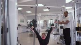 регистрация : Trainer helps female to stretch her body hanging on ropes in the gym. The lady corrects her body with physical training. Healthy lifestyle of young people Стоковые видеозаписи