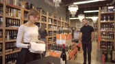 дегустация : Bottles are standing in alcohol shop. Girl in white shirt cleans wine glass. Man with tattoo comes and looks on bottles. Visitors are choosing drink