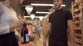 выборе : Pretty girl seller offers wine to the visitor. A bearded guy with tattoos on his arm wants to buy good wine at a liquor store. Стоковые видеозаписи