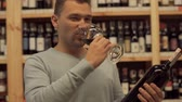 мерло : Handsome male is smelling wine in the glass. Man is holding bottle in the hand. Man tastes alcoholic drink and likes it. Customer is in alcohol shop