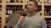 grape : Portrait of handsome man standing with glass of red wine in alcohol shop close up. Woman in the background is choosing wine bottle. Place with lot of alcohol drinks.