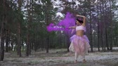 brilliance : Beautiful girl with bright makeup in a pink dress dancing with smoke bombs on the background of pine trees.