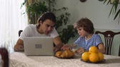 комментарий : Small cute boy sitting on the kitchen table eating croissant with cappuccino and older adult handsome brother watching laptop. Kid discuss with brother topic in computer. Стоковые видеозаписи