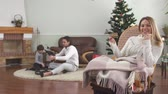cobertor : Pretty woman is sitting in arm-chair holding credit card. Father and little son playing with drone sitting on the floor in the background. Happy family celebrates Christmas at home