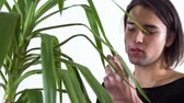 dudaklar : Man with lipstick on lips touching leaves of home plant and then looking in camera close up. Transgender man spends time alone. Studio shooting