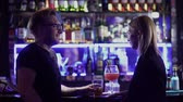 alcoholico : Adult couple drink cocktails at the bar counter. Man in glasses and blond woman talking at the disco and smiling. Having fun at night club Archivo de Video