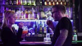 flashlight : Adult man meets blond woman standing near the bar counter and talks to her. Man in glasses and blond woman spend time at the disco. Having fun at night club