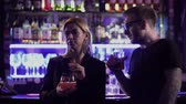 alcoholico : A handsome bearded guy in glasses with an alcoholic cocktail comes up to a girl standing with a cocktail at the bar counter. The man made an indecent proposal to the girl and the girl went away.