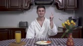 masa örtüsü : Confident smiling man in white bathrobe snapps his fingers and table with breakfast appears in front of him. Plate with fried eggs, orange juice and vase with tulips are on the table covered with checkered tablecloth Stok Video