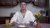 masa örtüsü : Attractive young man in a white bathrobe sitting at the kitchen table enjoying the aroma of breakfast. Stok Video
