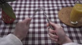 isteyen : Mans hand rub the knife on the fork, demanding food close up. Orange juice glass and vase are on the table with checkered tablecloth. Concept of feeding. First person shooting Stok Video