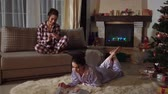 anno : Attractive young sisters twins relaxing in a cozy Christmas room in pajamas in evening chatting and reading magazines Filmati Stock