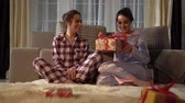 pigiama : Beautiful adult sisters twins exchanging Christmas or New Year presents with each other on cozy living room