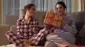 anno : Beautiful adult sisters twins exchanging Christmas or New Year presents with each other on cozy living room