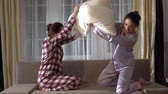 pigiama : Pretty sisters twins are having fun with laugh and smiles and fighting with pillows in the evening in a cozy living room