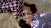 fofoca : Two pretty sisters twins in pajamas lie on the soft carpet facing each other and having lovely evening talk