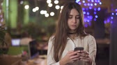 nošení : Portrait of confident young woman in white blouse formal wear texting message on cell mobile phone in modern office or cafe. Background blurred. Camera moves right