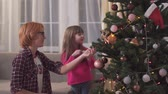 pomocník : A little girl helps her mother decorate the Christmas tree with toys.