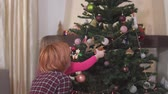 anno : A little girl helps her mother decorate the Christmas tree with toys.