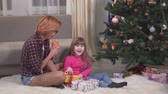 anno : Funny little girl and her mother sitting under the Christmas tree, holding some present boxes in hands and smiling. Young woman with short red hair and her child have fun together before holiday