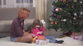 anno : Mom and daughter with gifts near the Christmas tree. Relationship mothers and daughters.