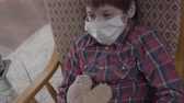 alergia : Little ill boy sitting in the armchair with medical mask on his face holding the toy at home. Different pills lying on the table on the background. Concept of healthcare. Camera moving down