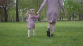 ランニング : Mother and small daughter running around with holding hands in amazing green park. Loving carring family.
