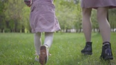 ランニング : Legs of a young mother and a little girl running in the park on the green grass holding hands close up. Active healthy lifestyle, connection with nature, carefree childhood 動画素材